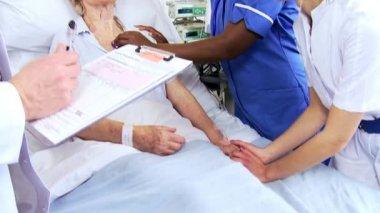 Multi etnické nemocniční personál ošetřujícím starší pacient — Stock video