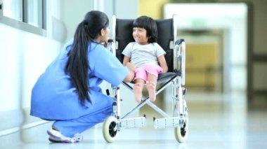 Asian Indian Nurse Talking Little Ethnic Girl Hospital Wheelchair — Stock Video