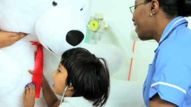 Child patient playing with stethoscope and teddy bear — Vídeo de Stock