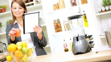 Businesswoman at kitchen using wireless tablet — Stock Video