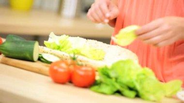 Girl at kitchen preparing submarine sandwich — Stock Video