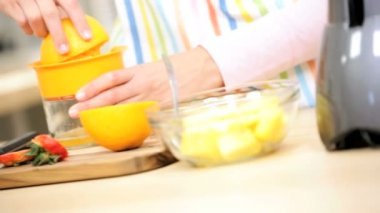 Girl at kitchen preparing orange juice — Stock Video