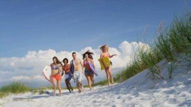 Teenagers carrying body boards across beach — ストックビデオ