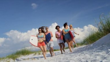 Teenagers carrying body boards across beach — Stock Video