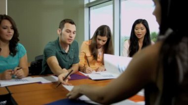 Students around table with female lecturer — Stock Video