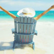 Girl in sun hat sitting on wood beach chair — Stock Video #56670231