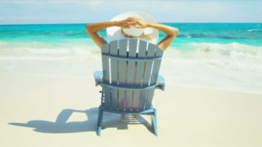 Girl in sun hat sitting on wood beach chair — Stock Video