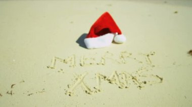 Santa hat lying on sandy beach — Vídeo stock