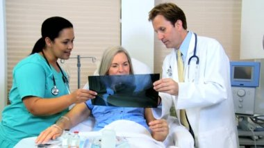 Female patient looking x-ray images with radiologist staff — Stock Video