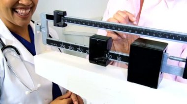 Nurse carrying out weight check of patient — Stock Video