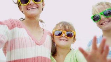 Girls on beach waving to camera — Stock Video