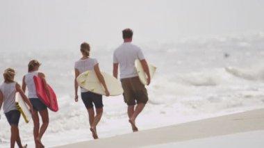Family walking across sandy beach — Stock Video