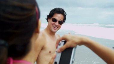 Couple on beach using camera — Stock Video