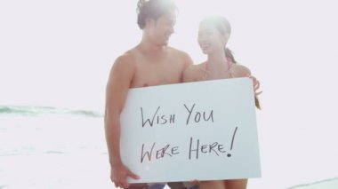 Couple on beach with white board — Stock Video