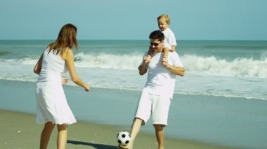 Parents with baby playing football on beach — Stock Video