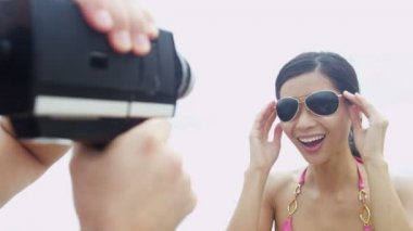 Couple on beach with video camera — ストックビデオ
