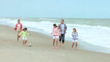 Family kicking ball on beach — Stock Video
