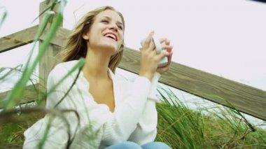 Girl on beach drinking coffee — Stock Video