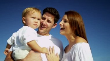 Parents holding son on sandy beach — Stock Video