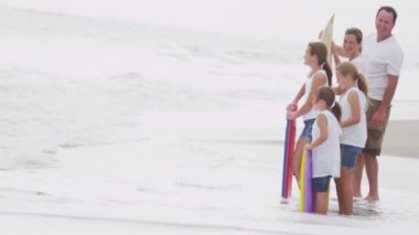 Family with bodyboards watching waves — Stock Video