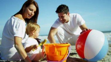 Föräldrar med son spelar på sandstranden — Stockvideo