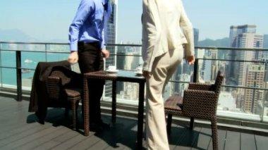 Business associates in rooftop restaurant — Stockvideo