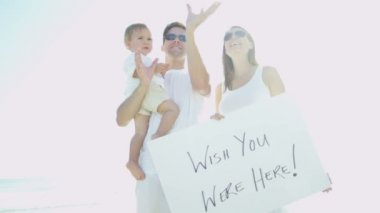 Family on beach holding message board — Stock Video