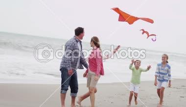 Family with flying kite on beach — Vídeo de Stock