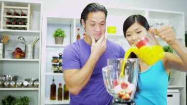 Couple putting ingredients to produce nutritious homemade organic fruit juice — Stock Video