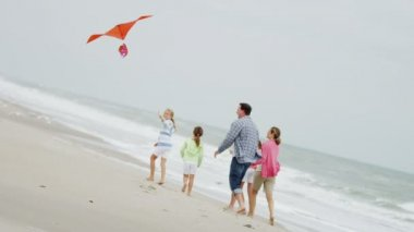 Family with flying kite on beach — Stock Video