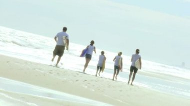 Family running with bodyboards on beach — Stock Video