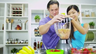 Couple putting delicious organic fruits into electric blender for fresh smoothie — Stock Video
