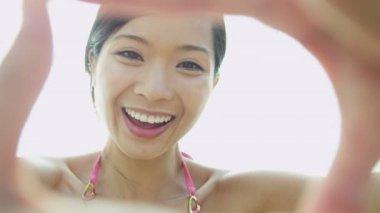 Woman on beach making finger frame — Stock Video
