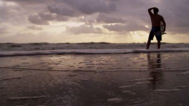 Surfer on beach watching waves — Stock Video