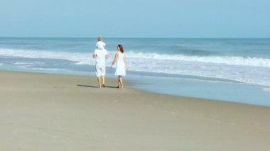Genitori con il bambino che cammina sulla spiaggia — Video Stock