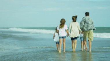 Genitori con figlie che camminano sulla spiaggia — Video Stock