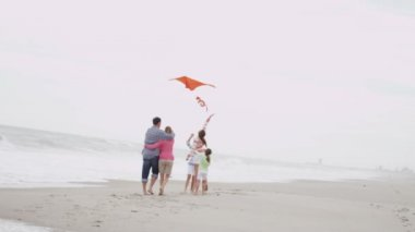 Family with flying kite on beach — Stockvideo