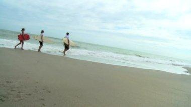 Famiglia che cammina con bodyboard sulla spiaggia — Video Stock
