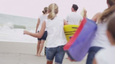 Girls running to parents watching waves — Stock Video