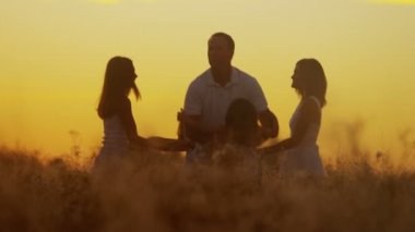 Parents with daughters on meadow at sunset — Stockvideo
