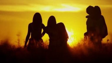 Parents with daughters on meadow at sunset — Stock Video