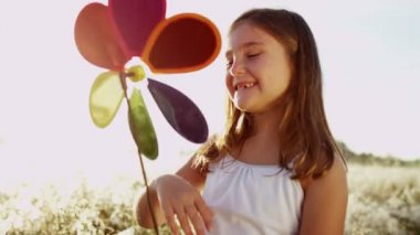 Girl outdoors playing with colorful windmill toy — Stock Video