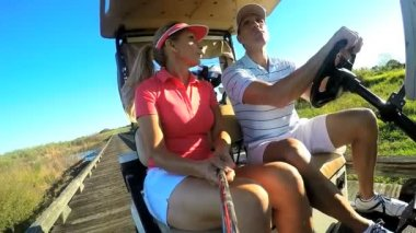 Couple of golf players driving buggy cart — Stock Video