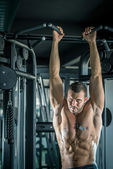 Man doing pull ups in gym — Stock Photo