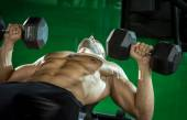 Man doing dumbbell press while lying down — Stock Photo