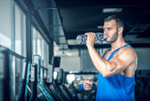 Young man drinking water in gym — Stock Photo