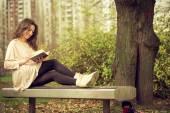 Flicka som läser en bok i parken — Stockfoto