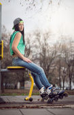 Girl sitting on gym machine with roller blades — Stock Photo