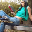 Girl in jeans reading a book on bench — Stock Photo #69755401