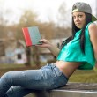 Girl in jeans reading a book on bench — Stock Photo #69755413